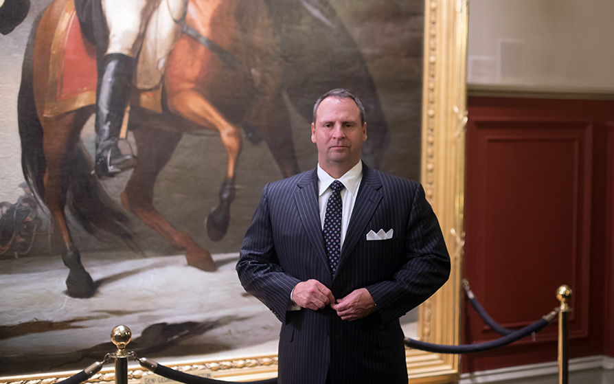 Man standing in a suit in front of a painting of a man riding a horse